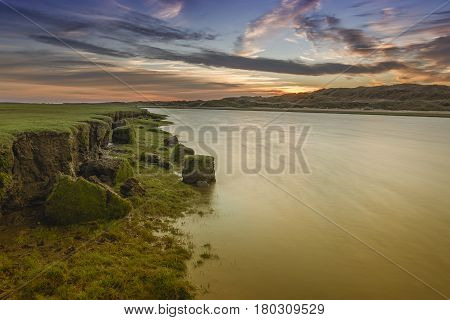 The river Ogmore, south Wales, at sunset. A slow shutter speed has smoothed out the river and the river bank looks to be eroding