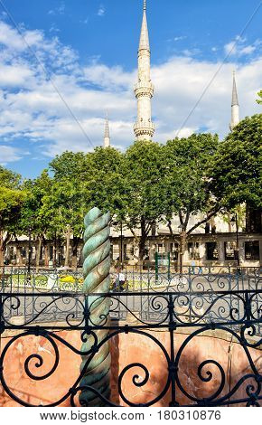 The famous greek Serpent Column in the ancient Hippodrome in Istanbul, Turkey. The minarets of the Blue Mosque in the distance.