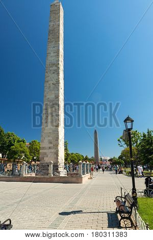 ISTANBUL - MAY 26, 2013: Tourists visiting the ancient Hippodrome in Istanbul, Turkey. The Walled Obelisk (front) and the Obelisk of Thutmosis III (back) are the greatest monuments of Byzantine Culture.