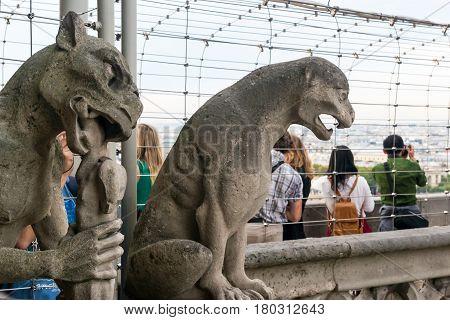 PARIS - SEPTEMBER 25, 2013: Chimeras (gargoyles) and tourists of the Cathedral of Notre Dame de Paris.