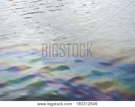 Oil slick creates muted rainbow on gray day