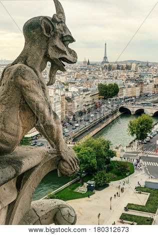 Chimera (gargoyle) of the Cathedral of Notre Dame de Paris overlooking the Eiffel Tower in Paris, France