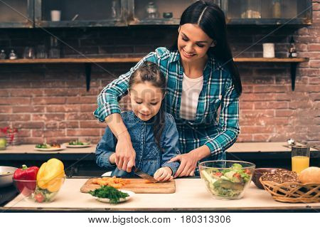 Time to cook together. Photo of mother and little daughter. Woman teaching girl how to cook. Table full of organic vegetables. They making fresh salad