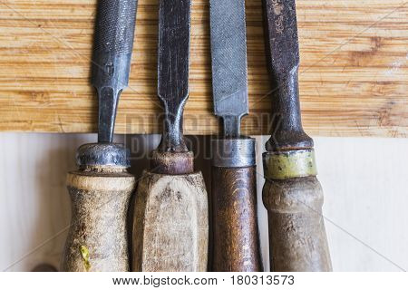 Vintage files and chisels with shabby wooden handles close-up lying two light and brown wooden boards. Man's tricks concept