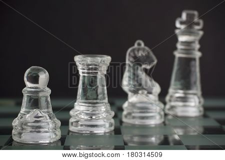 Glass chess team: king pawn knight and rook on black