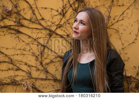 Modern young woman next to yellow wall with ivy in old europian city