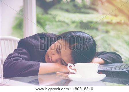 Business woman heavy workload sleep at office desk with finance sheet calculator and coffee. concept for overworked