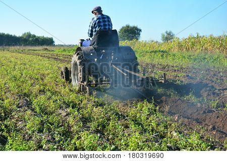 KIEV - UKRAINE APRIL - 12, 2017:  Farmer on tractor plowing. Farmer plowing field with tracktor.