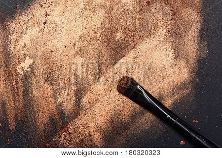 Make-up Art Brush on golden painted Surface with Particles of Eyeshadow