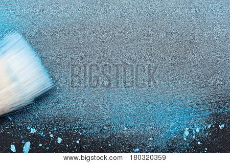 Make-up Artist's Brush on smudged blue Powder with Copy Space for Text