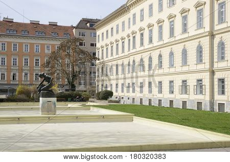GRAZ, AUSTRIA - MARCH 20, 2017: Sculpture of a kneeling woman with a dolphin in plaza of the city of Graz the capital of Styria Austria