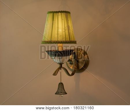 Old style lamp mounted on beige wall with lampshade