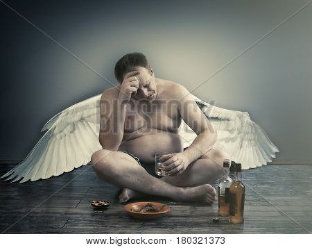 Male fallen angel with alcohol and a cigarette sitting on the floor. Habits way of life the temptations and trials