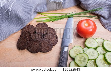 Pumpernickel in a glass bowl on a wooden board with knife tomato and cucumber