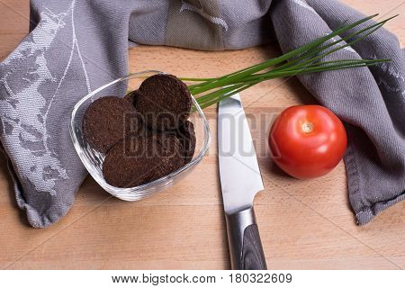 Pumpernickel in a glass bowl on a wooden board with knife and tomato
