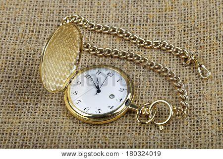 old golden pocket watch on burlap background