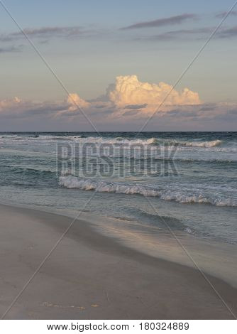 Sunset at a beautiful Florida beach with crisp surf and puffy pink clouds.