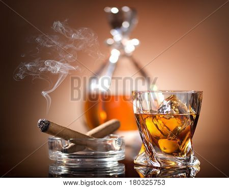 Glass of whiskey and a cigar in vintage style