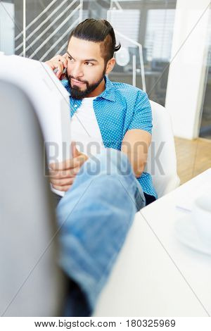 Young man with smartphone calling business hotline