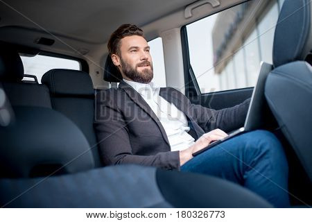 Handsome businessman working with laptop on the backseat of the car