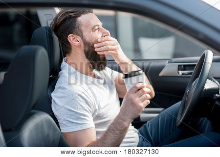 Tired man yawning on the front seat of the car holding coffee to go