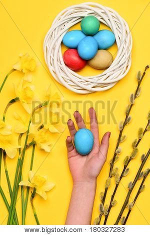Colorful Easter Eggs In Wreath With Willow And Yellow Narcissus