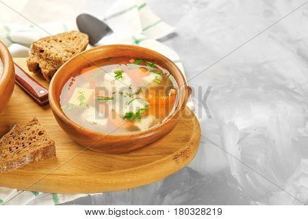 Crock pot with chicken soup on wooden board