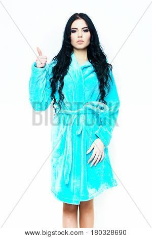 pretty serious cute sexy girl or beautiful woman showing cool with fashion makeup and curly long hair posing in turquoise velour bathrobe isolated on white background