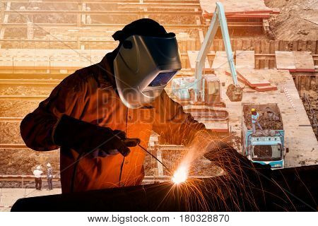 Welding Worker Welding Steel Structure With Construction Crane And Building At Construction Site For