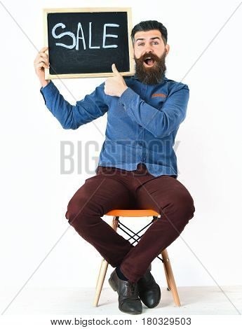 Bearded man long beard. Brutal caucasian amused hipster with moustache holding sale inscription on blackboard sitting on orange chair wearing blue shirt and vinous pants isolated on white background
