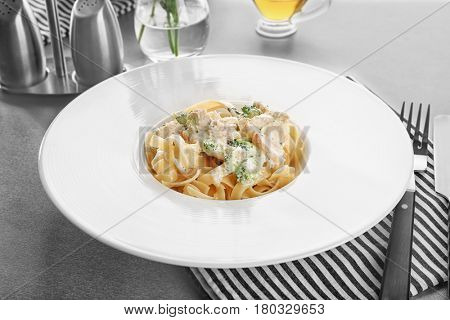 Plate of delicious pasta alfredo with chicken on table