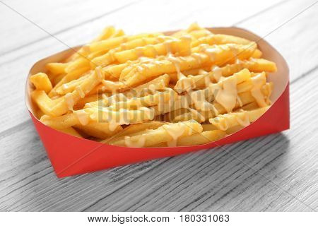 Paper red box full of delicious french fries with cheese sauce on white wooden background