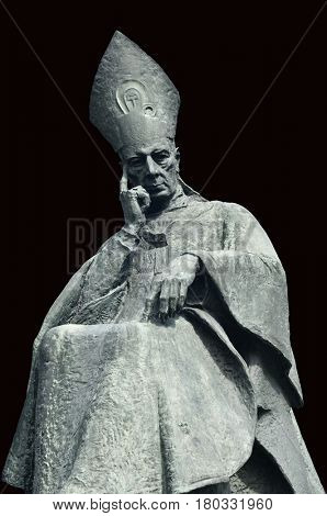 Cardinal bishop Wyszynski bronze monument in Warsaw. Isolated with path on black background.