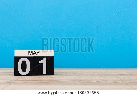 May 1st. Day 1 of month, calendar on blue background. Spring day, empty space for text. International Workers' Day.