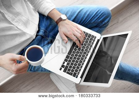 Young man with laptop and cup of coffee at home