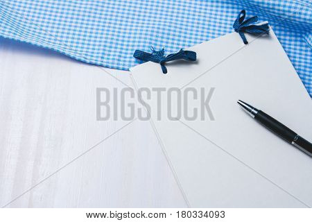 Blank daily notebook with pen and blue fabric on white wooden background