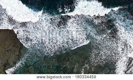 Top view of the huge ocean waves that crash against the rocky shore. Aerial view of the foam spray and turquoise sea water. View from above of the power of the ocean.
