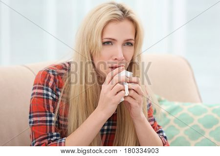 Young woman with allergy sitting on sofa at home