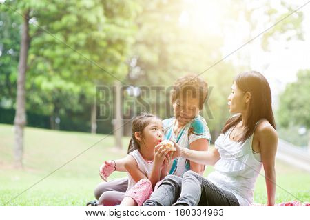 Candid portrait of multi generation Asian family at nature park. Grandmother, mother and daughter outdoor fun. Morning sun flare background.