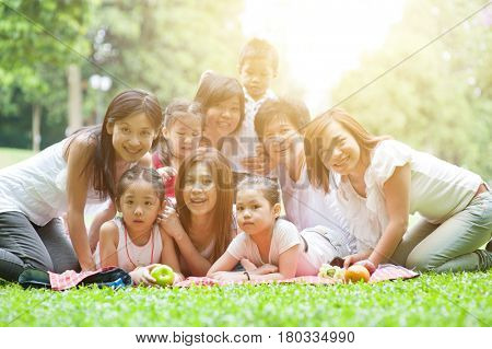Happy Asian multi generations family portrait, grandparent, parents and children, outdoor nature park in morning with sun flare.