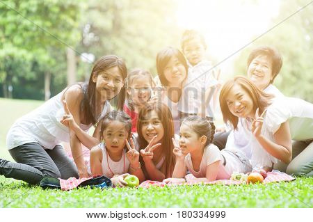 Cheerful Asian multi generations family portrait, grandparent, parents and children, outdoor nature park in morning with sun flare.