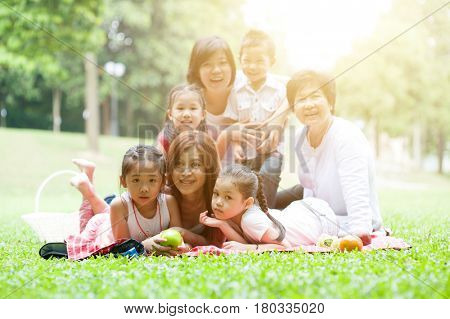 Asian multi generations family portrait, grandparent, parents and children, outdoor nature park in morning with sun flare.