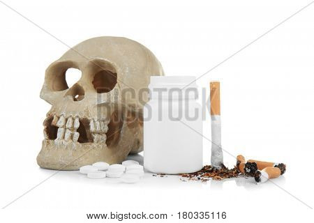 Skull, damaged cigarettes and pills isolated on white