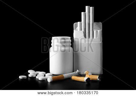 Damaged cigarettes, pack and drugs on black background