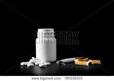 Damaged cigarettes and drugs on black background
