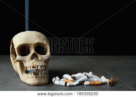 Skull and pile of cigarettes on black background