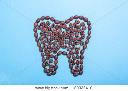 Unhealthy yellow teeth from coffee. Tooth from coffee beans on a blue background