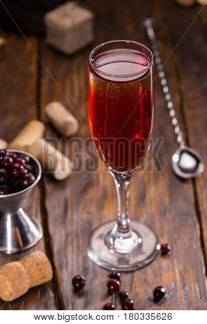 A glass of sparkling wine with liqueur and blackcurrant
