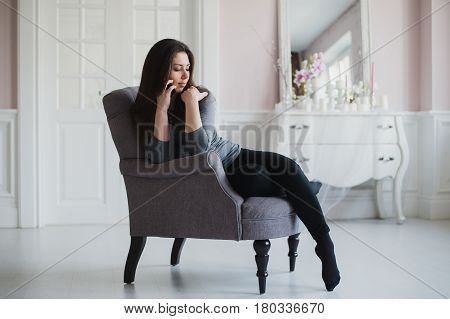 Shot of a casual woman talking with somebody on her mobile phone while sitting on armchair at home