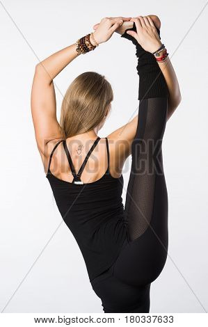 sports exercise isolated on white background. Beautiful woman dressed in sportswear, doing stretching legs. view from the back.